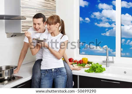 The young girl allows to try meal to the man at kitchen - stock photo