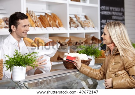 The young girl buys bread in shop