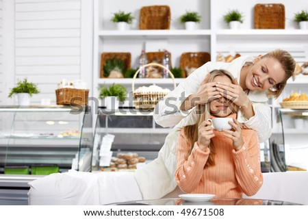 The young girl closes eyes to the girlfriend in cafe - stock photo