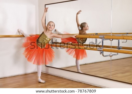 The young girl dances in a ballet orange tutu in the hall - stock photo