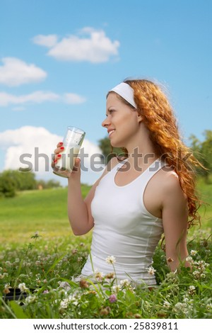 The young girl drinks milk in park against the sky