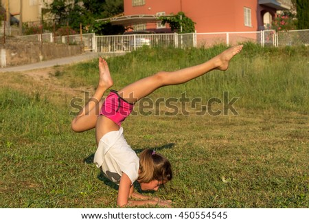 The young girl engaged in yoga, gymnastics on the grass. Healthy lifestyle.