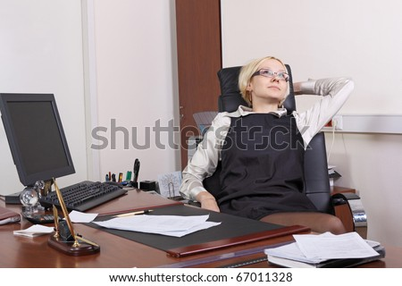 The young girl has relaxed in an armchair at office in the end of the working day - stock photo