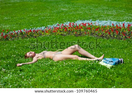 The young girl in a bathing suit sunbathes in park - stock photo