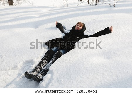 The young girl in a black fur coat lays in a snow