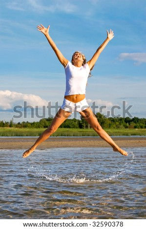 The young girl in a high jump from water - stock photo