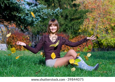 The young girl in autumn park during a leaf fall