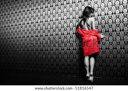 The young girl in red with a naked back on a black-and-white background - stock photo