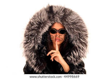 The young girl in sunglasses and a fur hood, to symbols silence - stock photo