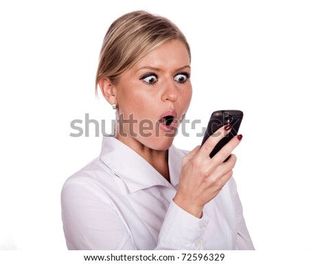 The young girl is holding a cell phone and looking at the screen with a surprised expression - stock photo