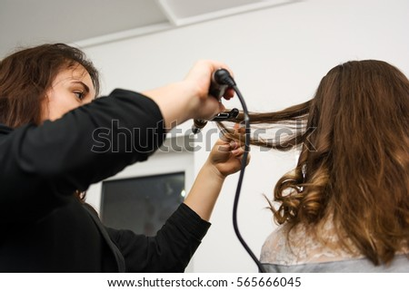 The young girl makes hairstyle to model using curling iron