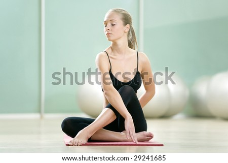 The young girl meditates in sports to a gym - stock photo