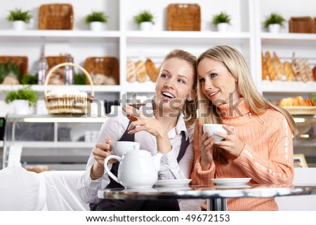 The young girl shows on something to the girlfriend in cafe - stock photo