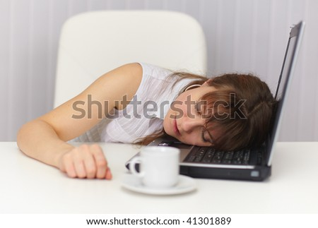 The young girl sleeps having placed a head on the laptop keyboard - stock photo