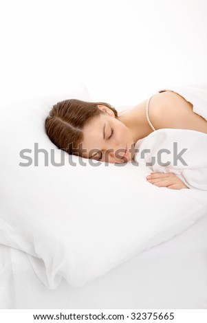 The young girl sleeps in the white bed, isolated - stock photo