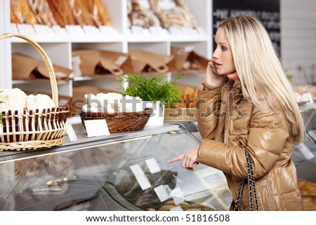 The young girl speaking on the phone does purchases in shop