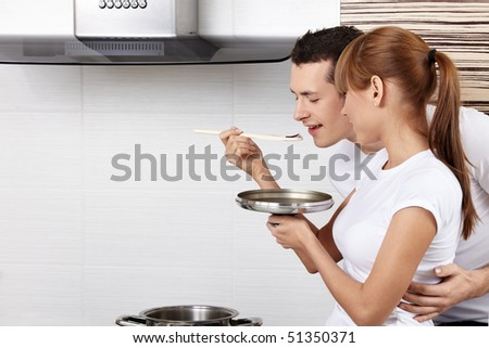 The young girl spoon-feeds the man on kitchen - stock photo