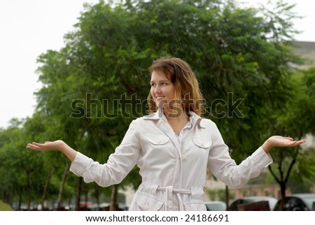 The young girl standing under a rain - stock photo