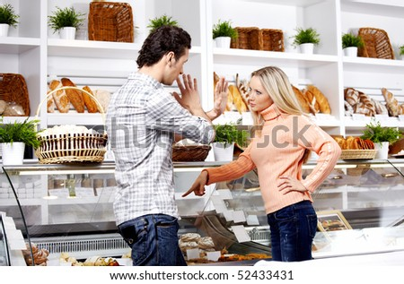 The young girl swears at the man in shop - stock photo