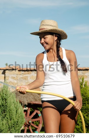 The young girl the farmer watering from a hose - stock photo