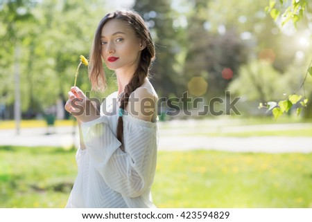 the young girl with a dandelion in hands about a birch in park