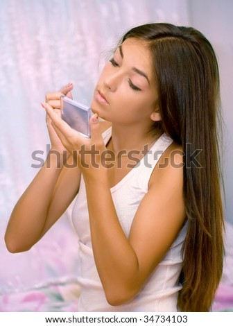 The young girl with a mirror on a pink background - stock photo