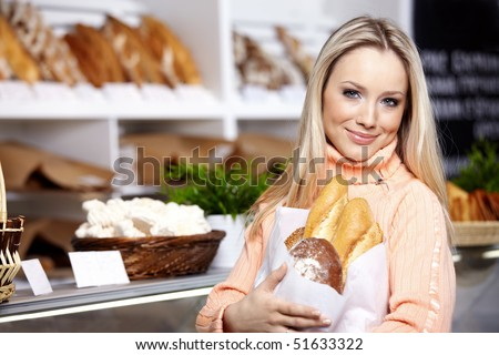The young girl with bread in shop - stock photo
