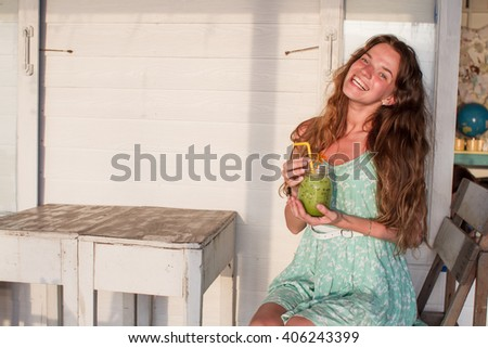 the young girl with long hair dressed in a green dress, Sitting in cafe on the seashore