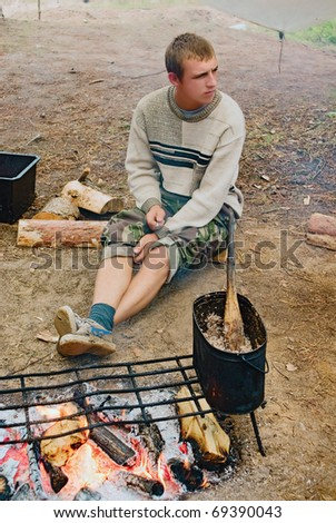 The young guy-cook at a campfire with a buckwheat cereal kettle