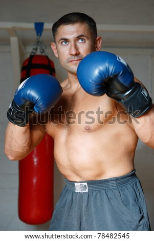 The young guy in the sports form boxes in gloves a pear - stock photo