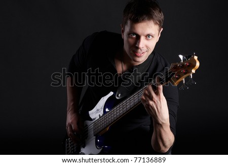 The young guy plays on a bass guitar - stock photo
