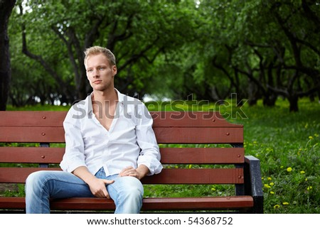 The young guy sits on a bench in park - stock photo