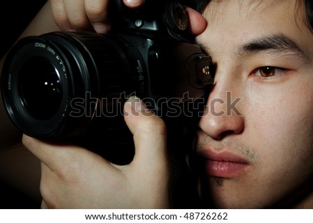 The young guy the photographer with the camera looks in the view-finder, an obverse portrait - stock photo