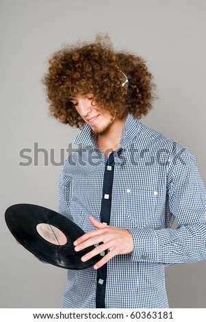 The young guy with a curly hair listens to music - stock photo