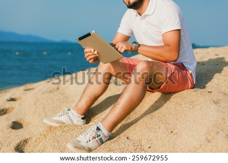 the young guy working on the tablet in sunglasses on the sea sitting on the beach - stock photo