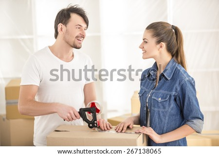 The young happy couple packing boxes. Moving, purchase of new habitation. - stock photo