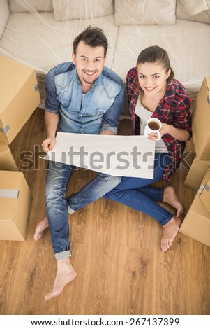 The young happy couple planning a new house. Moving, purchase of new habitation. - stock photo