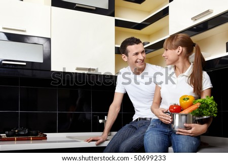 The young happy couple sits at kitchen - stock photo
