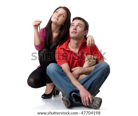 The young happy family with kitten and house keys in hands on a white background. House purchase concept. - stock photo
