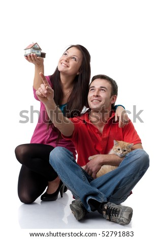 The young happy family with kitten holds house model in hands on a white background. House purchase concept.