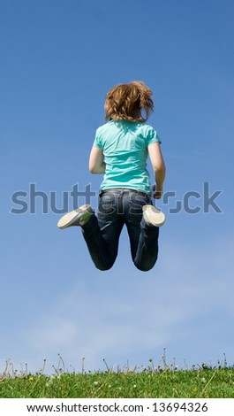 The young happy jumping girl on a background of the blue sky