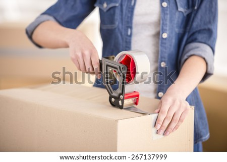 The young happy woman packing boxes. Moving, purchase of new habitation. - stock photo