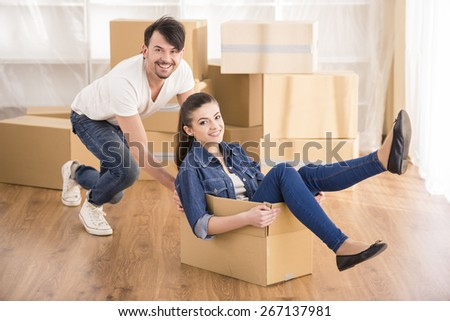 The young happy woman sitting in a cardboard box. Moving, purchase of new habitation. - stock photo