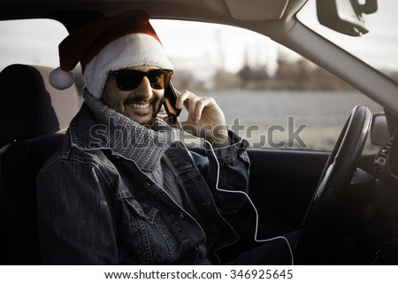 The young hipster santa claus use his mobile in the car color effect