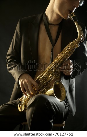The young jazz man plaing a saxophone on black - stock photo