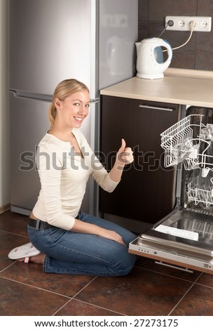 The young joyful woman sits near to the dishwasher on kitchen - stock photo