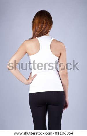 The young long-haired girl in a white vest on a grey background - stock photo