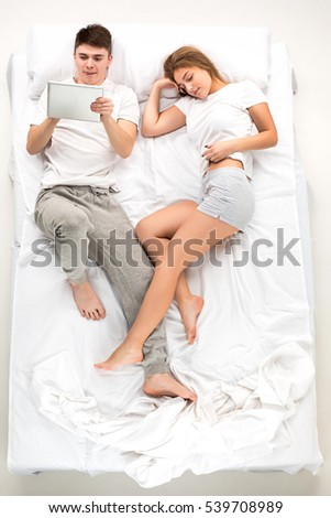 The young lovely couple lying in a white bed with laptop, love lconcept, top view