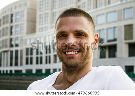 The young man against the background of the building.Young man smiling