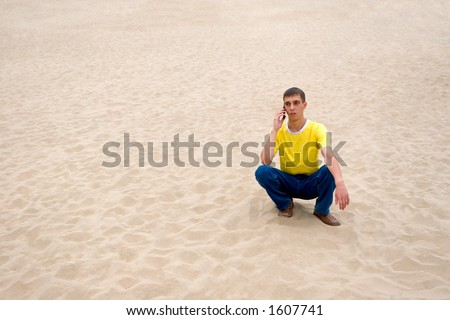 The young man and mobile on sand. - stock photo